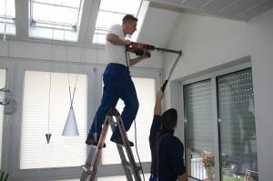 Moški pripravlja luknjo za montažo klimatske naprave