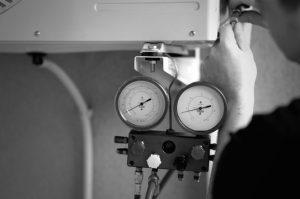Moški opravlja demontažo zunanje enote klimatske naprave